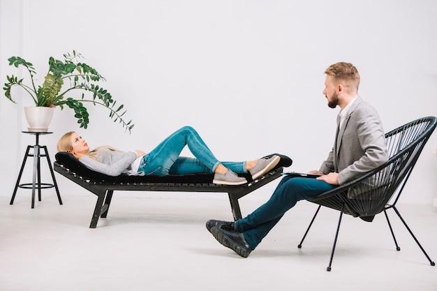 Psicóloga profesional conduciendo a consulta femenina tendida en el sofá.