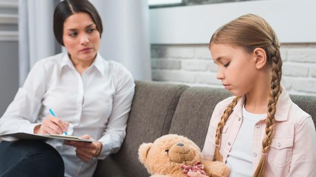 Psicóloga profesional joven que trata de comunicarse con una niña con problemas.