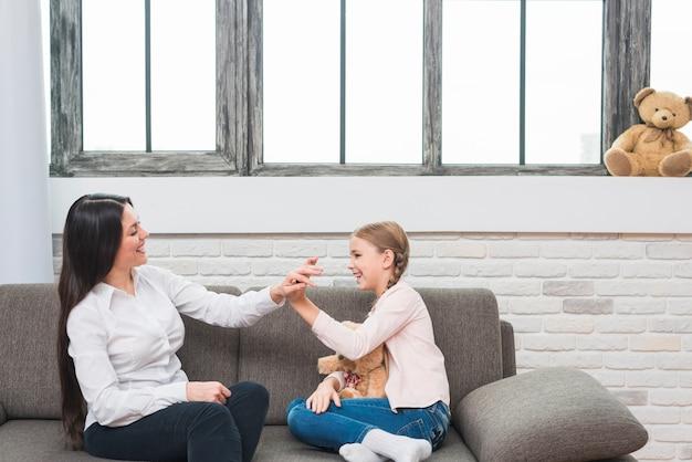 Psicóloga de sexo femenino feliz que da el alto cinco a la niña que se sienta en el sofá en casa