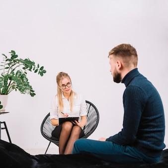 Psicóloga teniendo sesión con su paciente en el cargo.