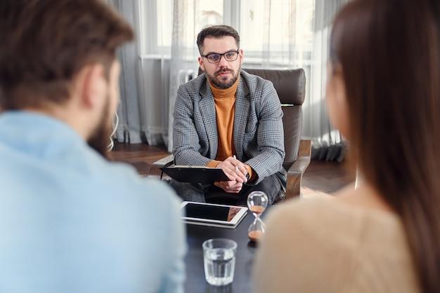 Psicólogo calificado escucha los problemas familiares de la joven pareja infeliz.