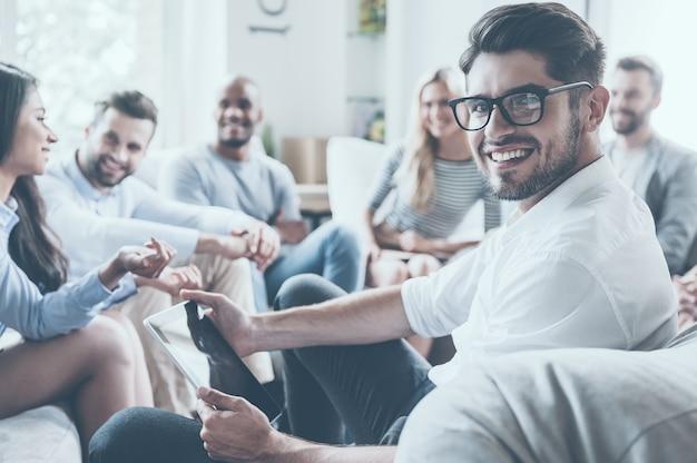 Psicólogo confiado. grupo de jóvenes alegres sentados en círculo y discutiendo algo mientras joven sosteniendo tableta digital y mirando por encima del hombro con una sonrisa