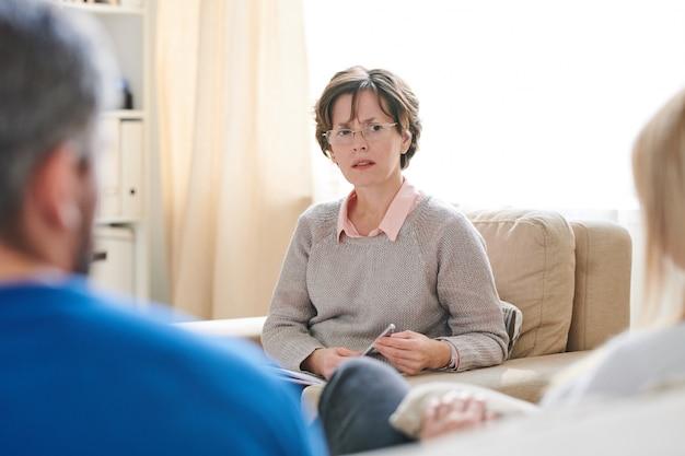 Psicólogo desconcertado escuchando a la pareja casada