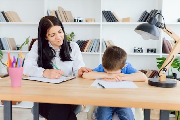Psicólogo infantil que asiste a un niño pequeño