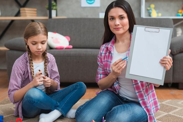 Psicólogo profesional de sexo femenino que se sienta con la muchacha en la alfombra que muestra el libro blanco en el tablero