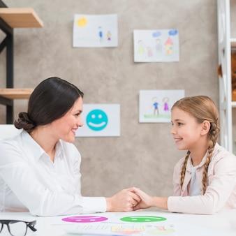 Psicólogo de sexo femenino que lleva a cabo las manos de la niña sonriente con la tarjeta feliz y triste de la emoción en la tabla