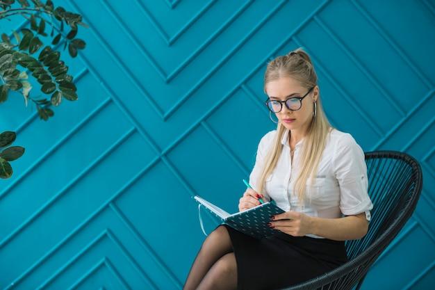 Psicólogo de sexo femenino que se sienta contra la escritura azul de la pared del diseño en el diario con la pluma