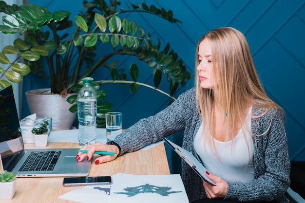 Psicólogo de sexo femenino rubio joven que usa el ordenador portátil en clínica