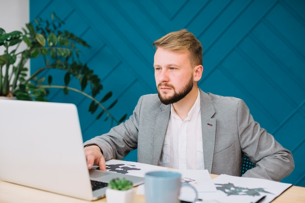 Psicólogo de sexo masculino joven que usa el ordenador portátil con los papeles de prueba de la mancha de tinta del rorschach en la tabla