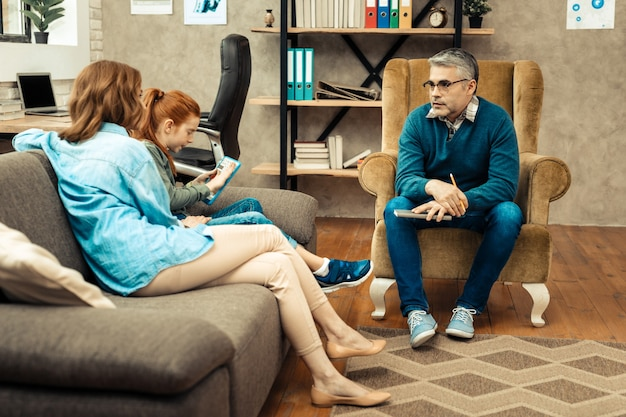 Psicoterapeuta experimentado. hombre inteligente inteligente mirando a sus pacientes mientras tiene una sesión psicológica con ellos