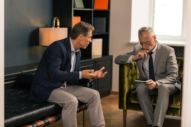 Psicoterapeuta serio sentado en su oficina mientras escucha a su cliente preocupado y mira notas en su bloc de notas