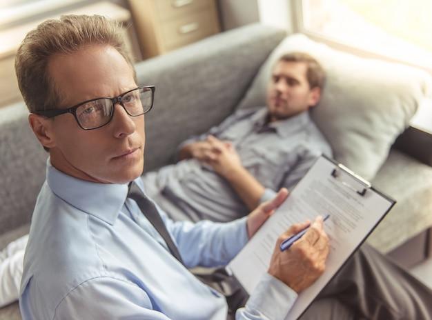 Psicoterapeuta en traje y anteojos está tomando notas.