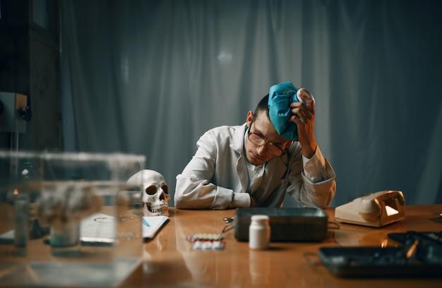 Psiquiatra hombre cansado en bata de laboratorio sentado en la mesa, hospital psiquiátrico. médico en clínica para enfermos mentales