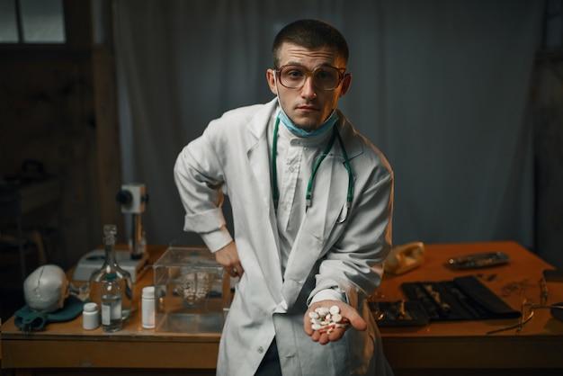 Psiquiatra masculino en bata de laboratorio muestra pastillas sedantes, hospital psiquiátrico. médico en clínica para enfermos mentales