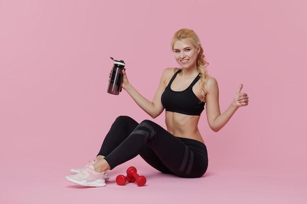 Publicidad entrenamiento personal. una joven deportiva bebe un batido de proteínas de una coctelera después de entrenar en el interior. pared rosa
