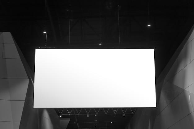 Publicidad interior en la feria o evento. tablero de promoción colgando con señalización blanca vacía