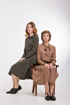 Publicidad de moda para mujer, vestido, zapatos. dos niñas felices sonriendo. retrato de mujeres abrazándose.