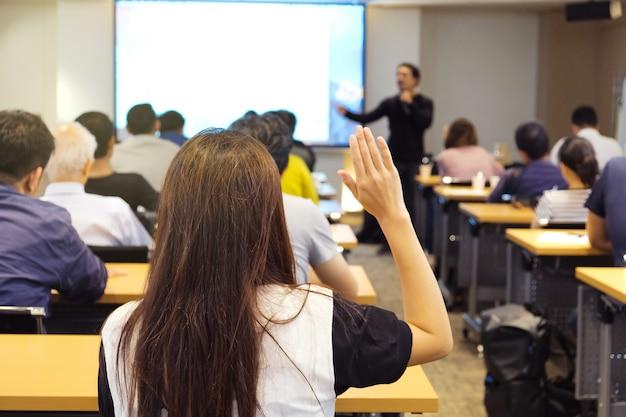Público levantando la mano y escuchando al orador que está de pie frente a la sala