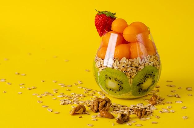 Pudín de chía con kiwi, avena y bolas de melón o papaya en un vaso sobre amarillo