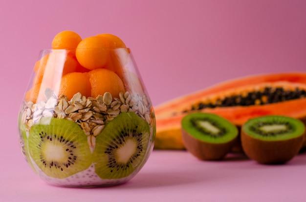 Pudín de chia con kiwi, avena y bolas de papaya en un vaso sobre púrpura