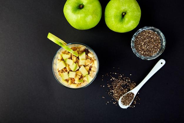 Pudín de chía saludable con manzanas y granola en vidrio.