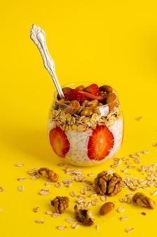 Pudín de yogur de chía con fresas, avena y nueces en un vaso sobre amarillo