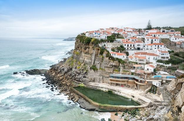 Pueblo blanco de azenhas do mar en el acantilado y el océano atlántico