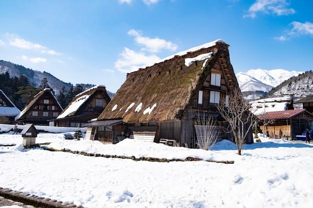 Pueblo en japón, cubierto de nieve en invierno y con un fondo azul cielo.
