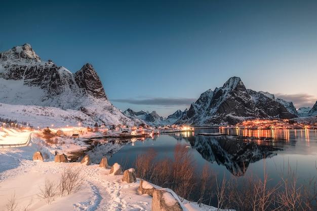 Pueblo de pescadores iluminado en la reflexión del valle de montaña en invierno al amanecer