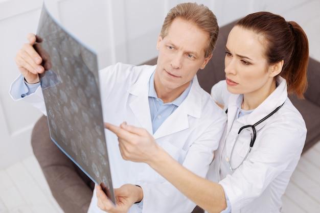 Puede que haya un problema. neurocirujanos entrenados con experiencia que examinan escáneres cerebrales del paciente mientras los sostienen a contraluz y buscan la causa de la enfermedad.