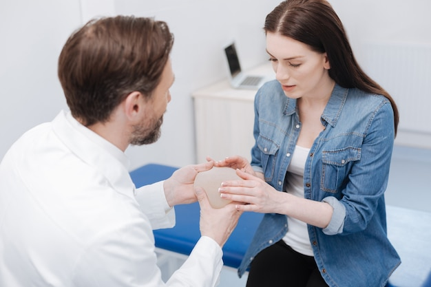 Puedes tocarlo. impresionante mujer inteligente comprometida que quiere aumentar sus senos mientras visita a un especialista y prueba varios implantes