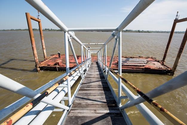 Puente de acero en el ducto del río embarcadero cargando petróleo y gas