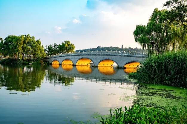 El puente de arco de piedra está en el parque.