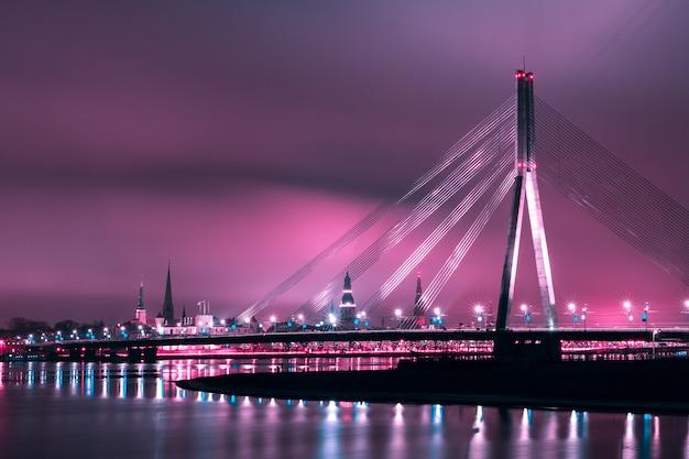 Puente atirantado y el río daugava en la noche, riga, letonia