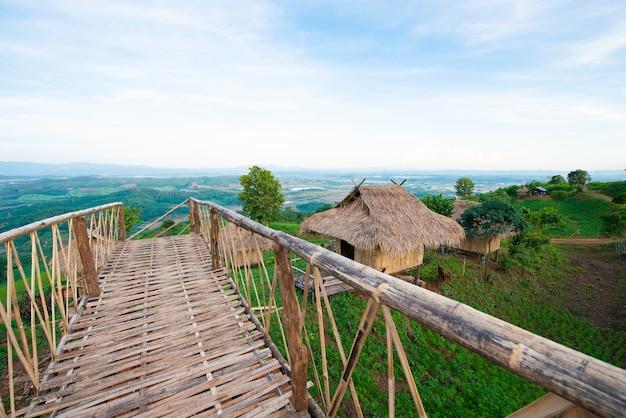 Puente de bambú y cabaña en la montaña con cielo azul
