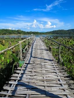Puente de bambú a través del lago de loto con fondo de montaña y cielo azul