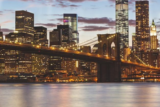 Puente de brooklyn y rascacielos en el centro de nueva york al atardecer