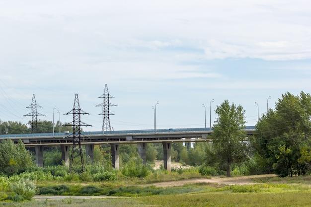 Puente de carretera que pasa por un campo con árboles y arbustos. panorama.