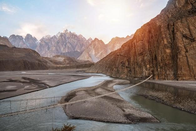 Puente colgante de hussaini sobre el río hunza, rodeado de montañas.