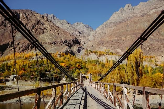 Puente colgante de madera conduce a la aldea de khalti en la temporada de otoño contra la cordillera del hindu kush