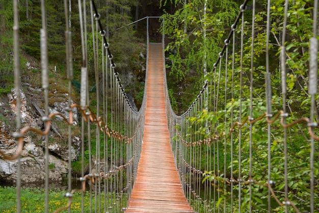 Puente colgante de madera sobre un río en un bosque