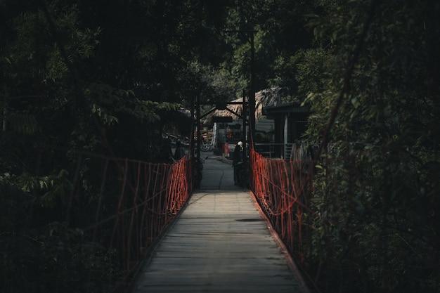 Un puente colgante rojo en el bosque.
