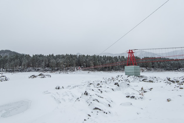 Puente colgante suspendido sobre el río congelado de invierno