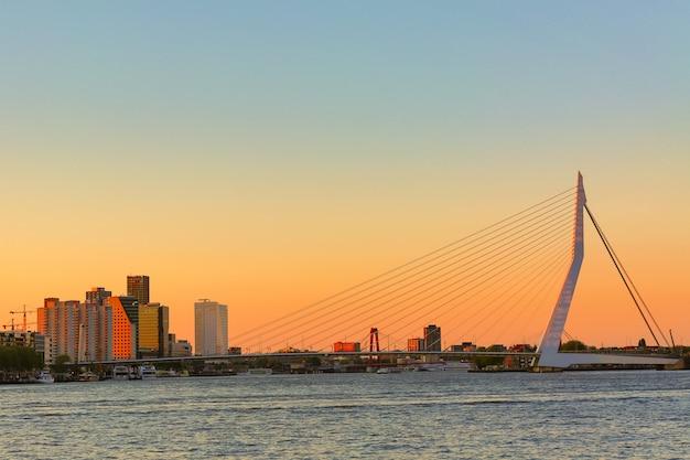 Puente erasmus sobre el río mosa con rascacielos en rotterdam, holanda meridional, países bajos durante el atardecer crepuscular.
