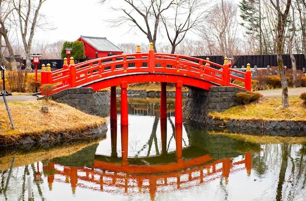 El puente está hecho de madera roja con un hermoso reflejo en el agua en japón