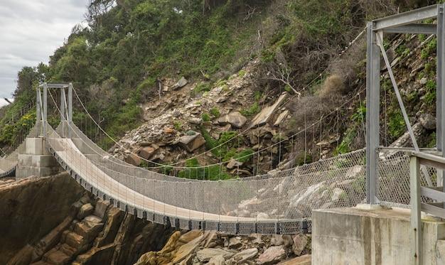 Puente de madera y metal que rodea la montaña.