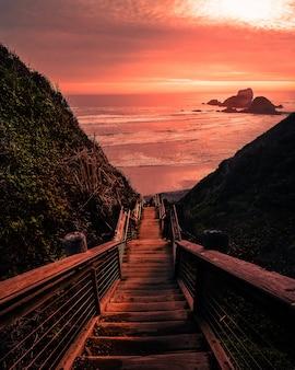 Puente de madera a la playa durante la puesta de sol
