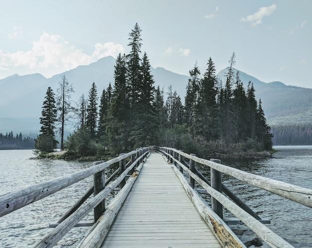 Puente de madera sobre el agua hacia el bosque con montañas