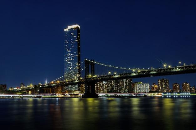 Puente de manhattan con la ciudad de rascacielos de brooklyn nueva york sobre el río hudson nueva york, hermosa escena nocturna
