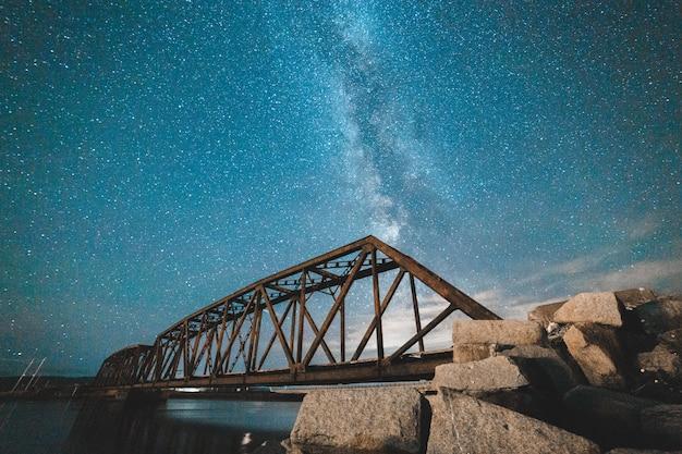 Puente de noche con cielo estrellado.